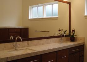 Master bath double vanity with custom wood trim around the mirror.