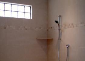 Custom walk in shower with center above head Rain shower, side wall shower heads, custom tile, and glass block window.