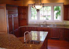 Granite counters, wood panel doors for appliances, raised bar island.