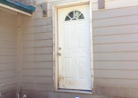 Compromised door and siding. Electrical not installed, no paint, no walk way.